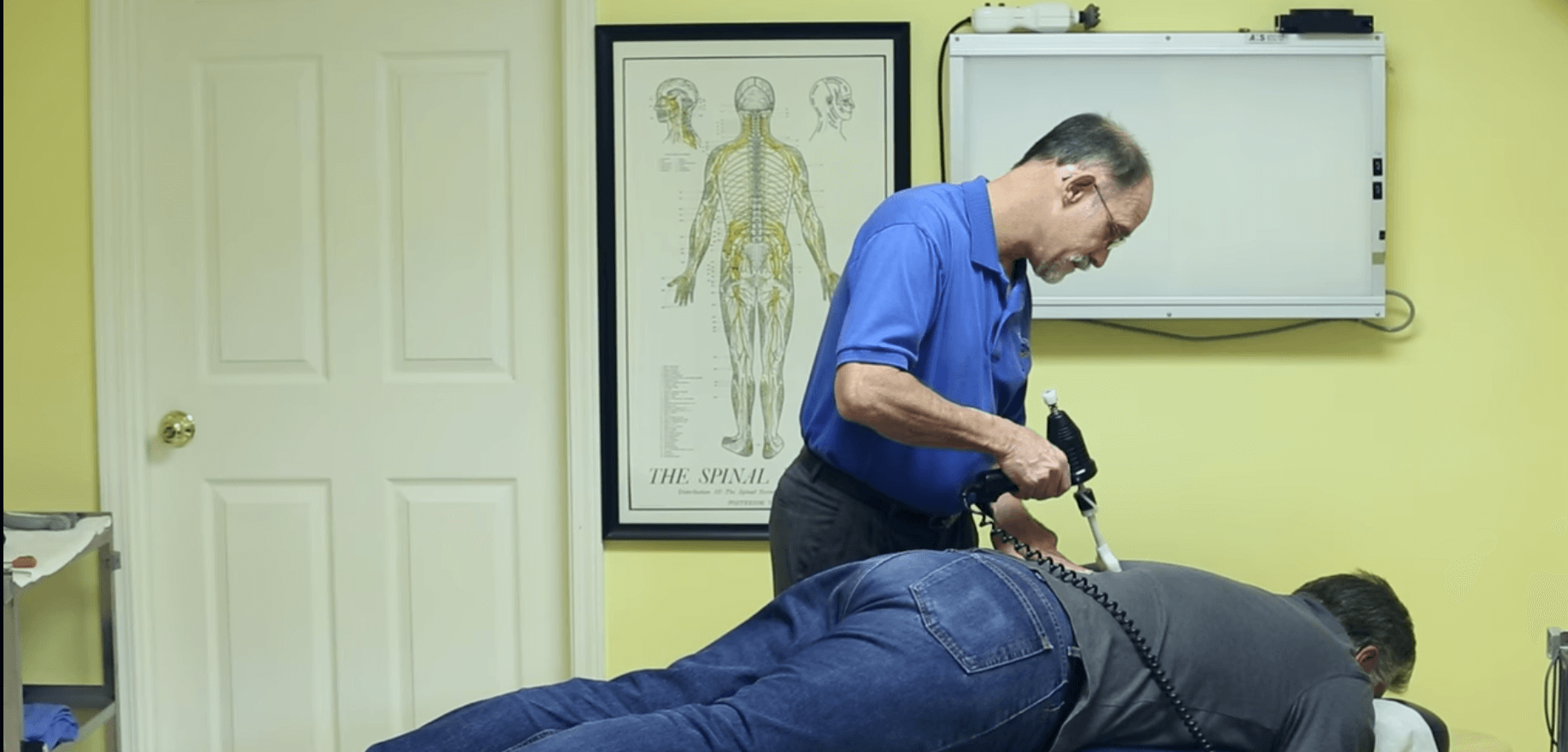 dr. chris helping lower back pain relief for patient